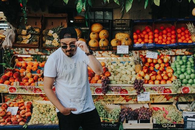 man-standing-beside-assorted-fruits-2042085